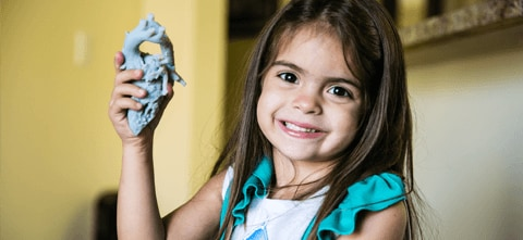 A young girl, holding a 3D printed medical model of her own heart that was used for Surgical planning