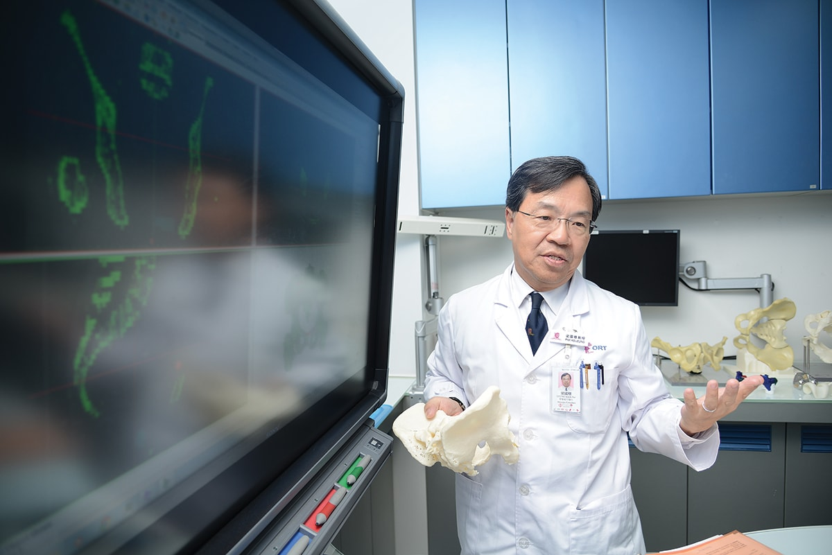 Doctor holding 3d printed bones near computer screen